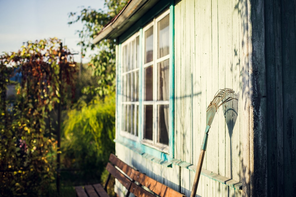 garden rake leaning on white wooden wall at daytime
