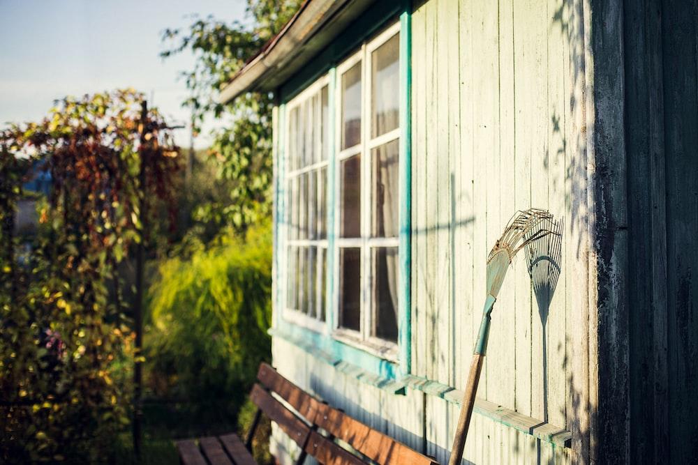 garden rake leaning on white wooden wall at daytime