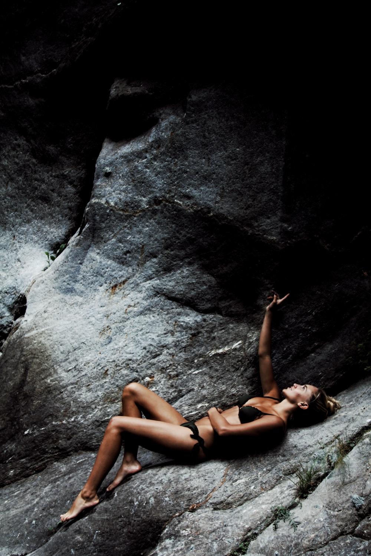 woman wearing black bikini lying on rock