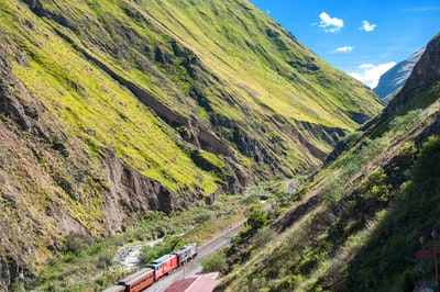 train on railway between green mountains during daytime ecuador zoom background