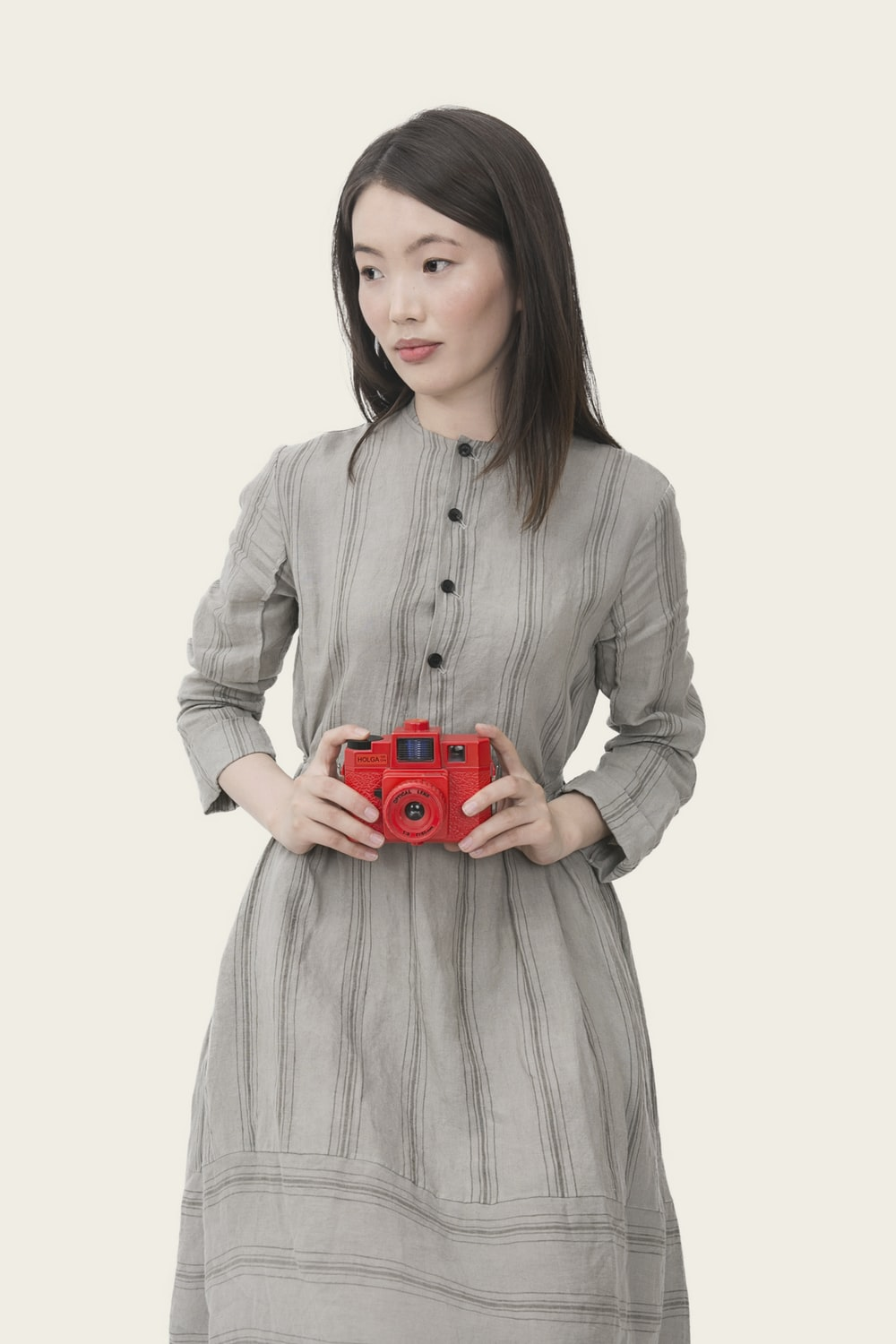 woman wearing gray striped button-up long-sleeved dress holding red point-and-shoot camera