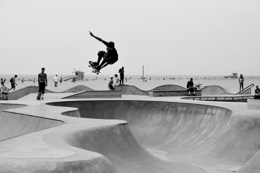 grayscale man skateboarding on skate park