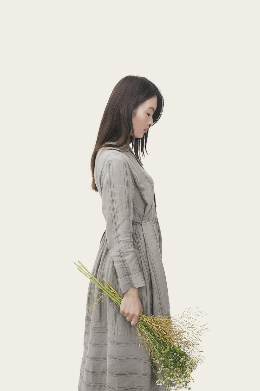 woman wearing grey dress holding flowers