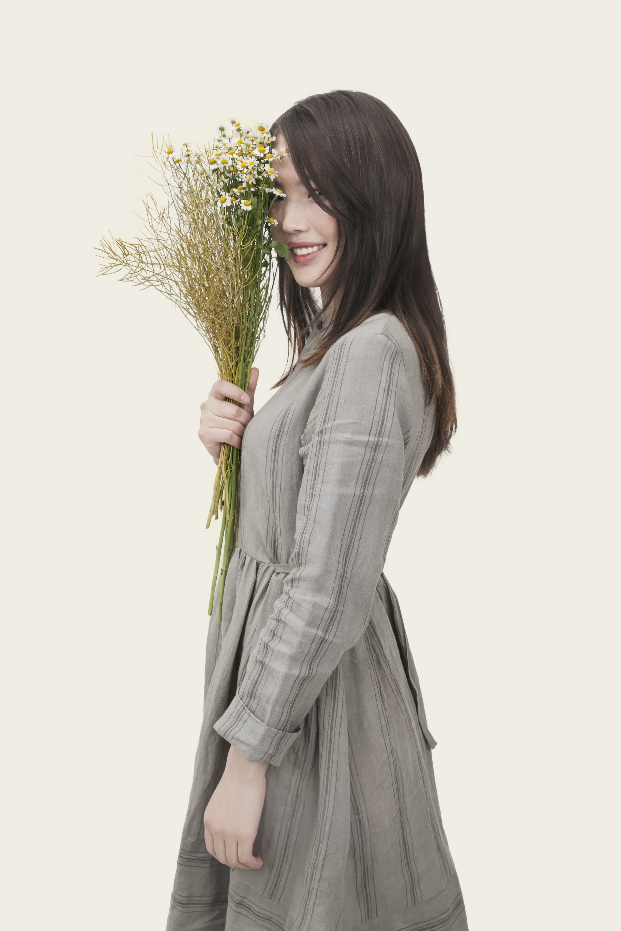 A happy Asian woman looking at the camera while holding a bouquet of flowers.