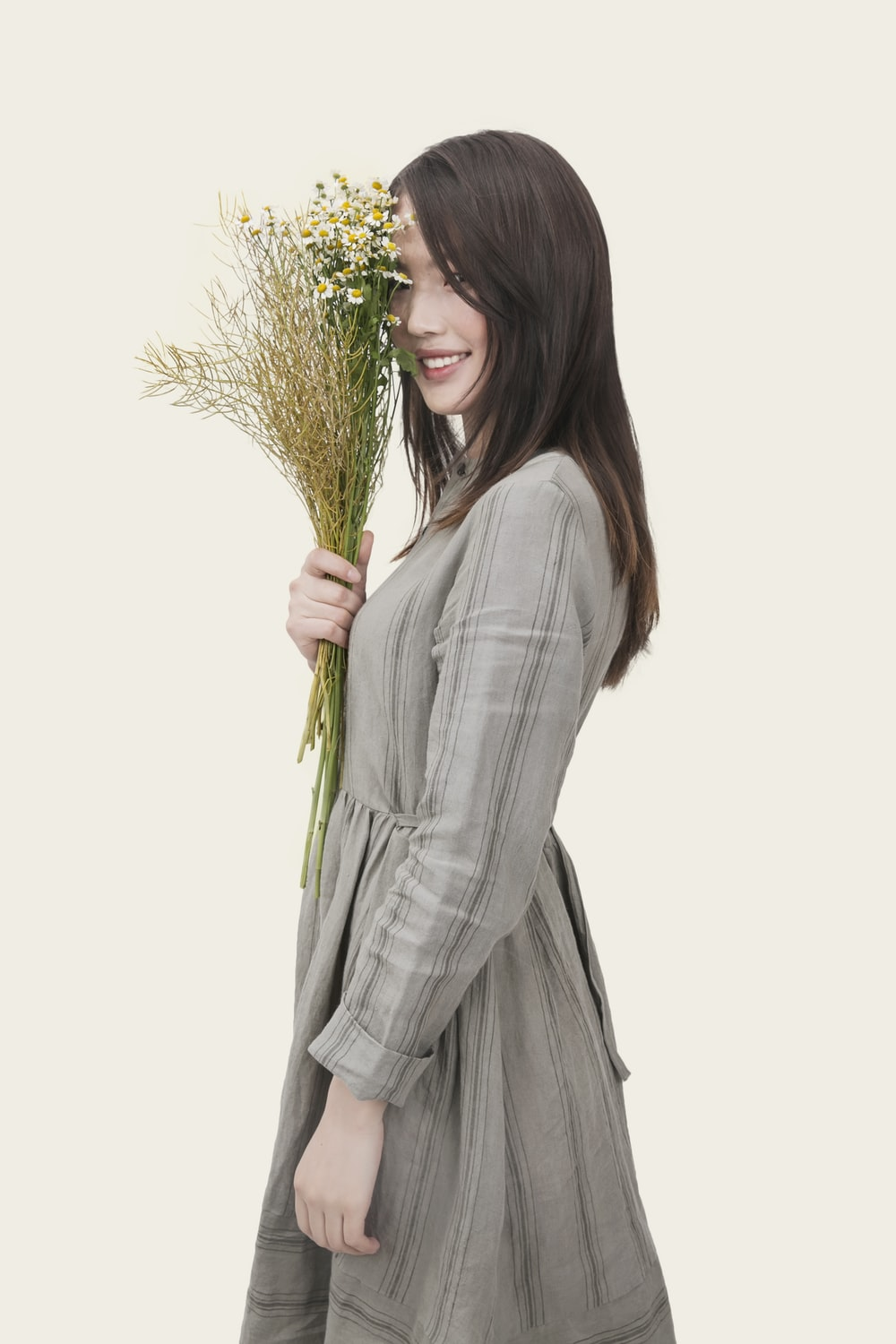woman wearing gray and black striped long-sleeved dress holding white petaled flowers