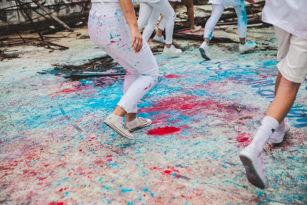 people stepping on floor with blue and red splattered paints