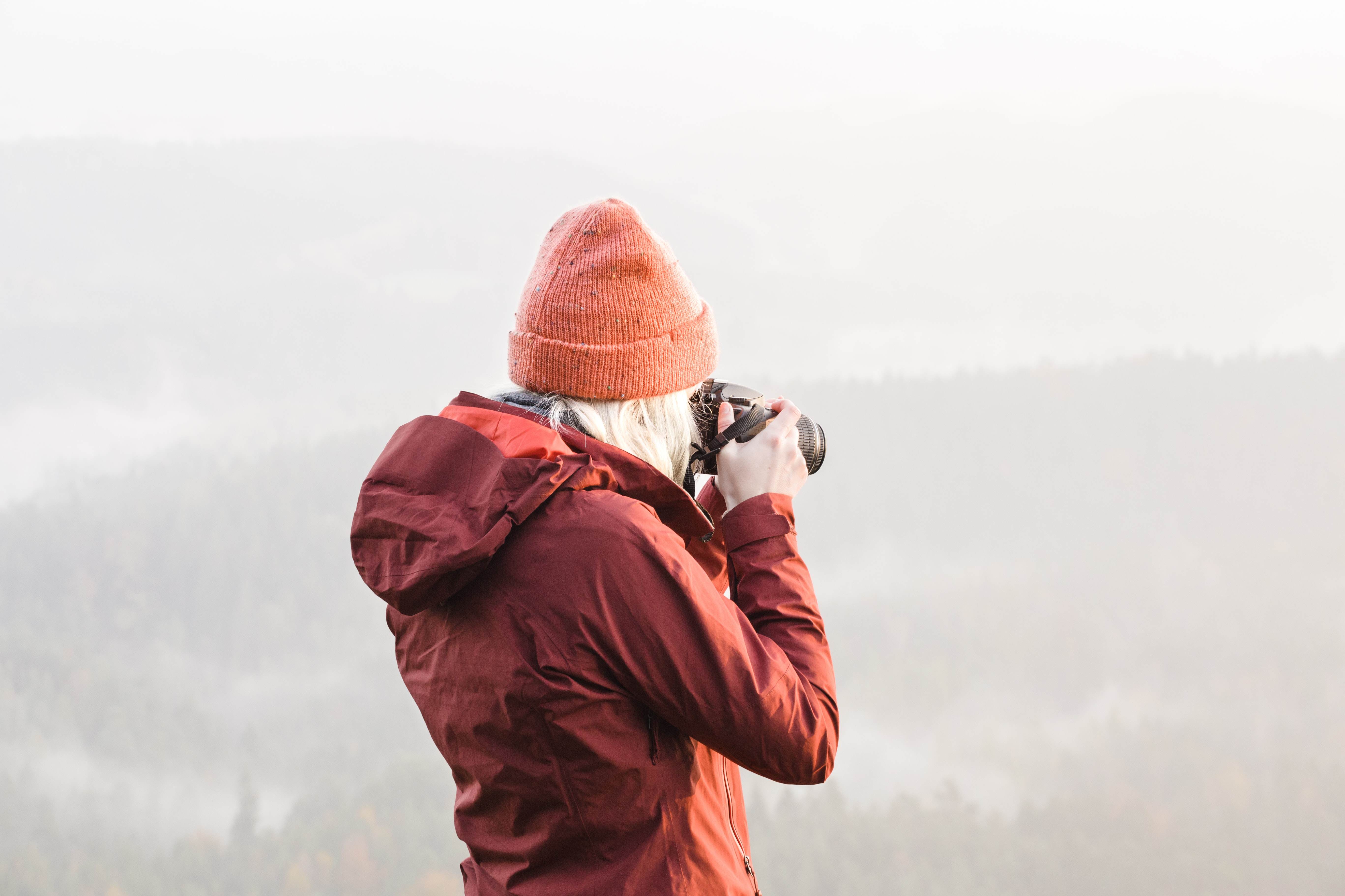 A woman photographing from on top of a mountain.