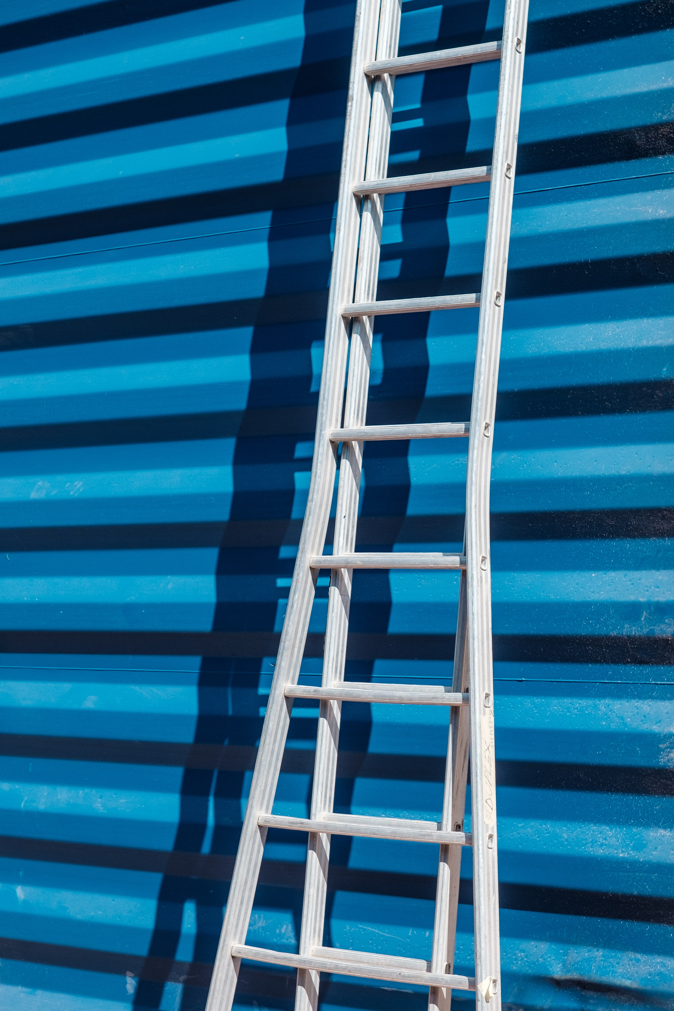 gray metal ladder leaning on blue corrugated sheet