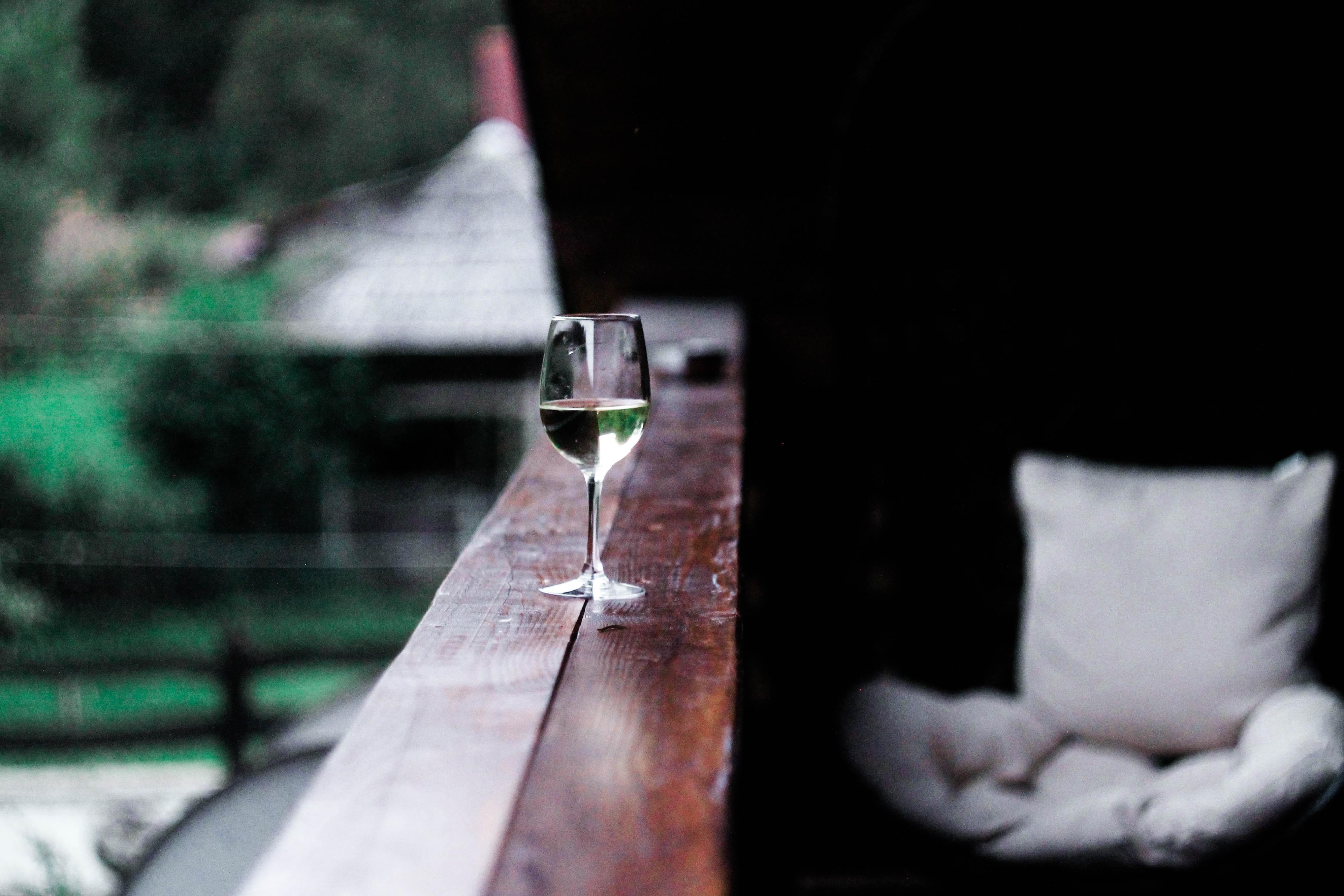 wine glass on wooden terrace rail