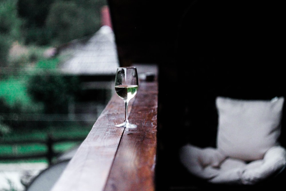 wine glass on wooden terrace rail