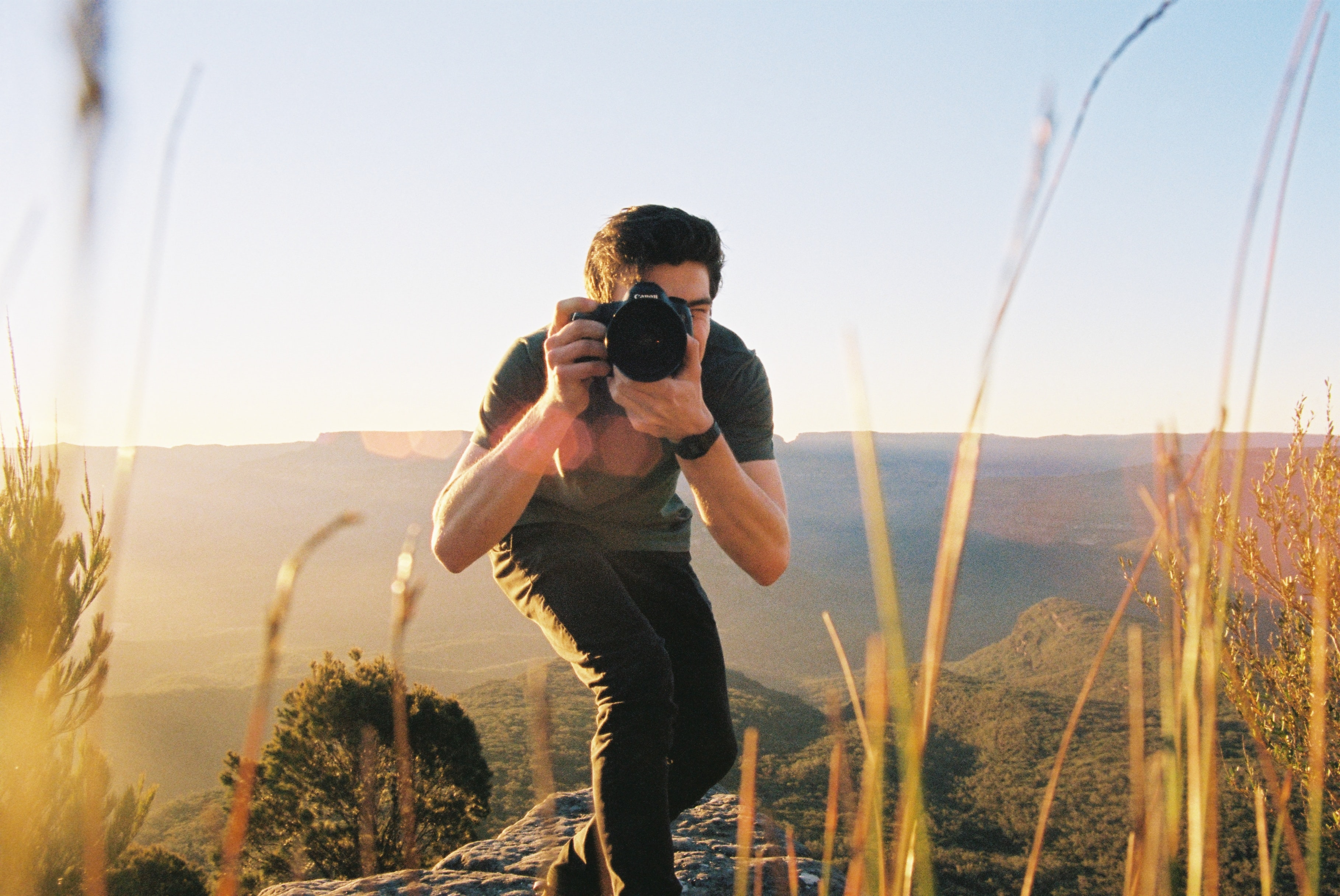 Photographer crouches with a camera to take a desert picture