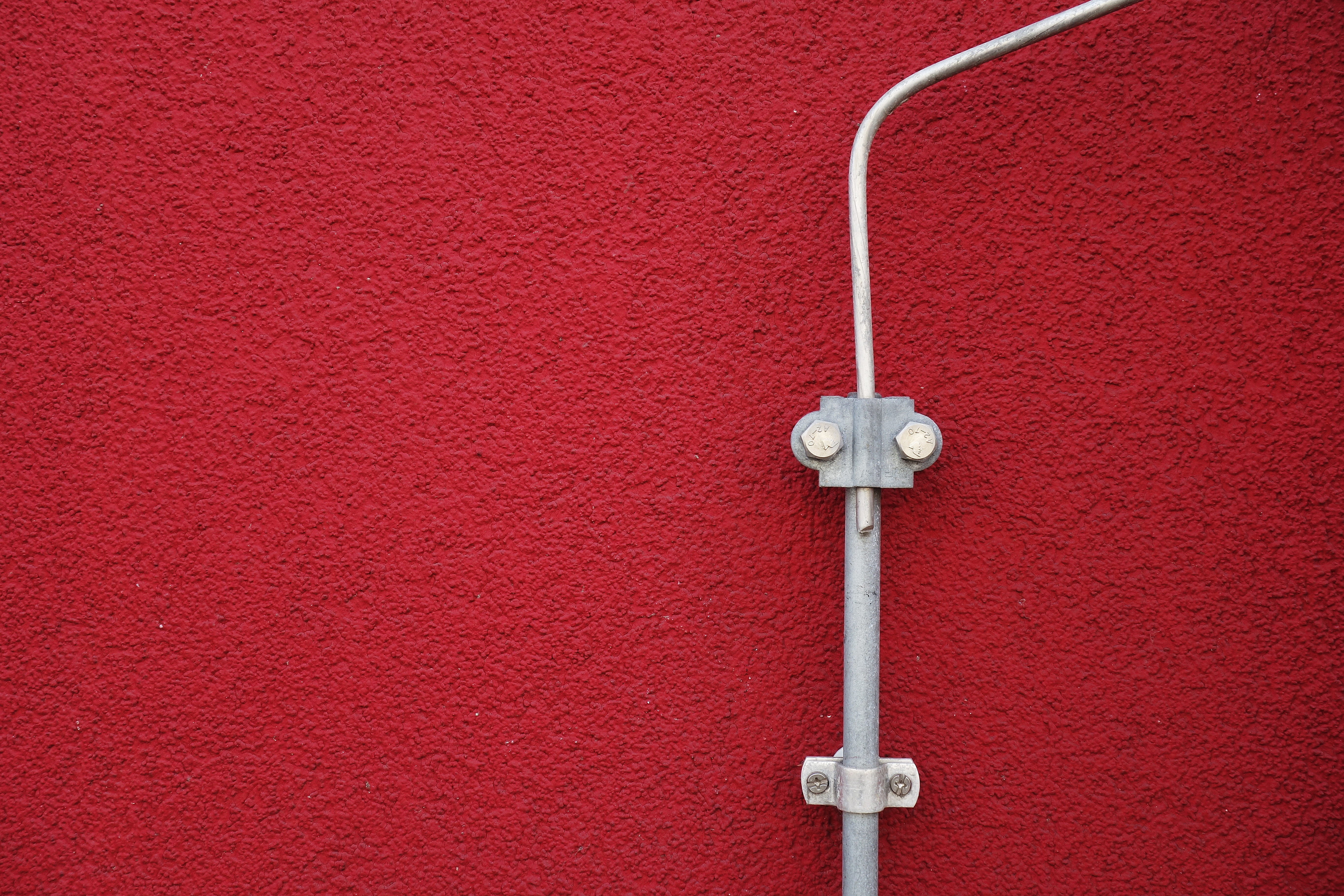 gray metal tube mounted on red surface