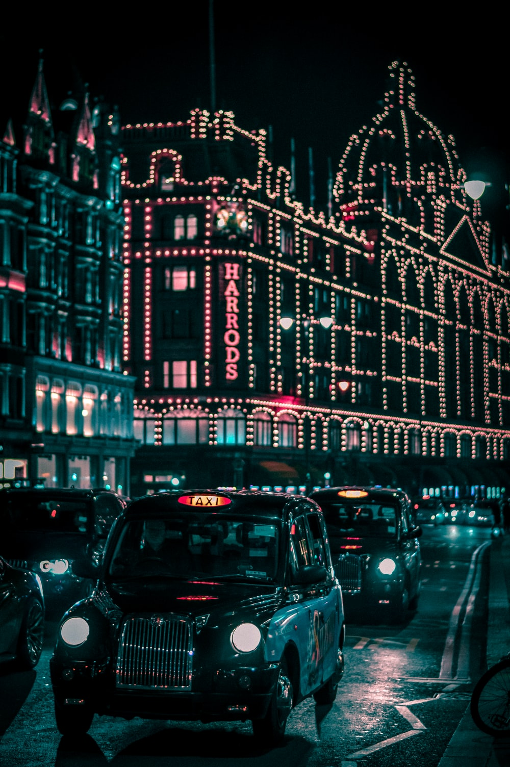 black taxi in the street passing trough Harrods Mall during nighttime