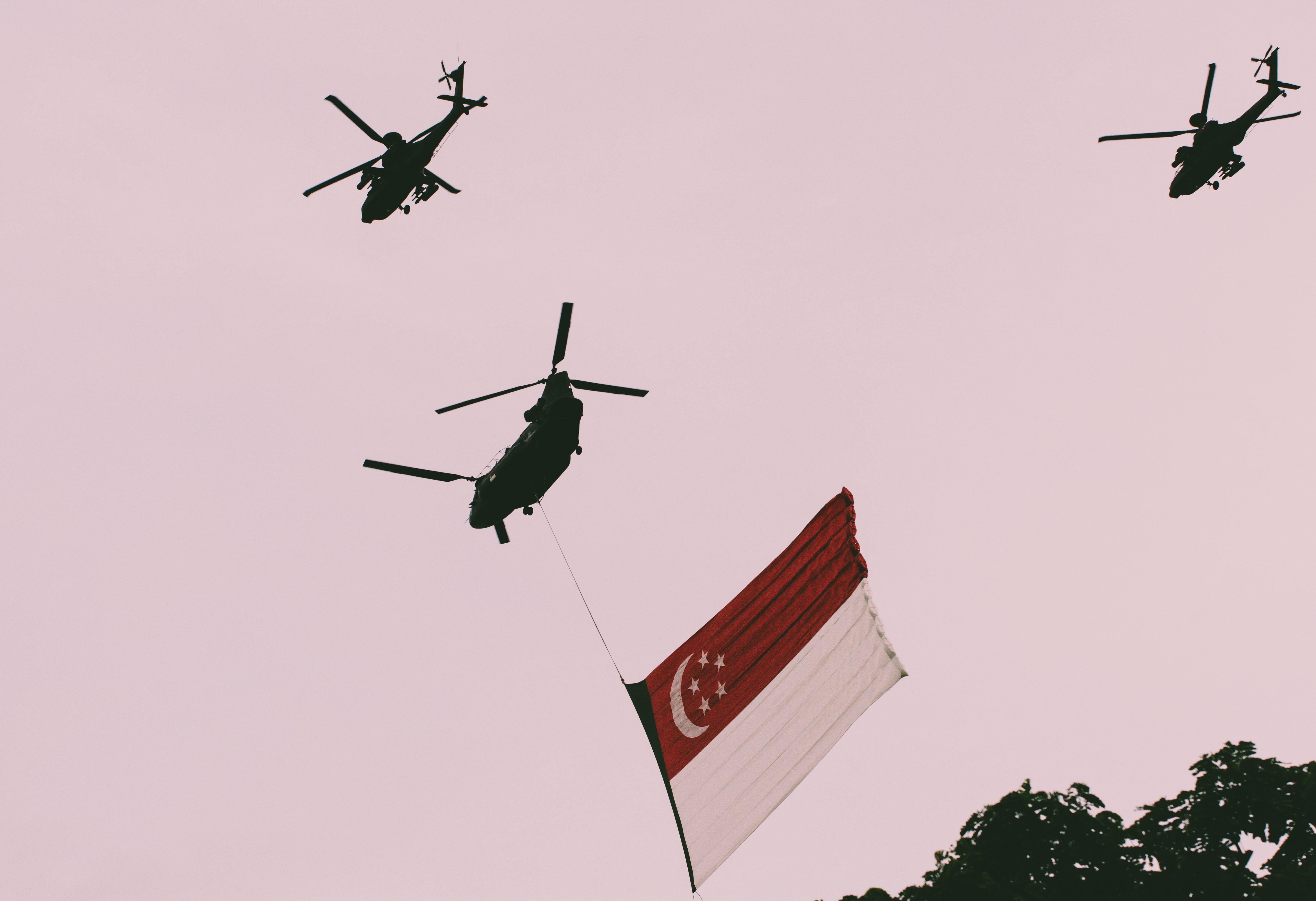 photo of three helicopters and one with flag