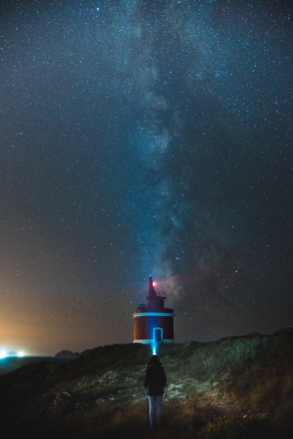 person walking towards red and white lighthouse under starry sky