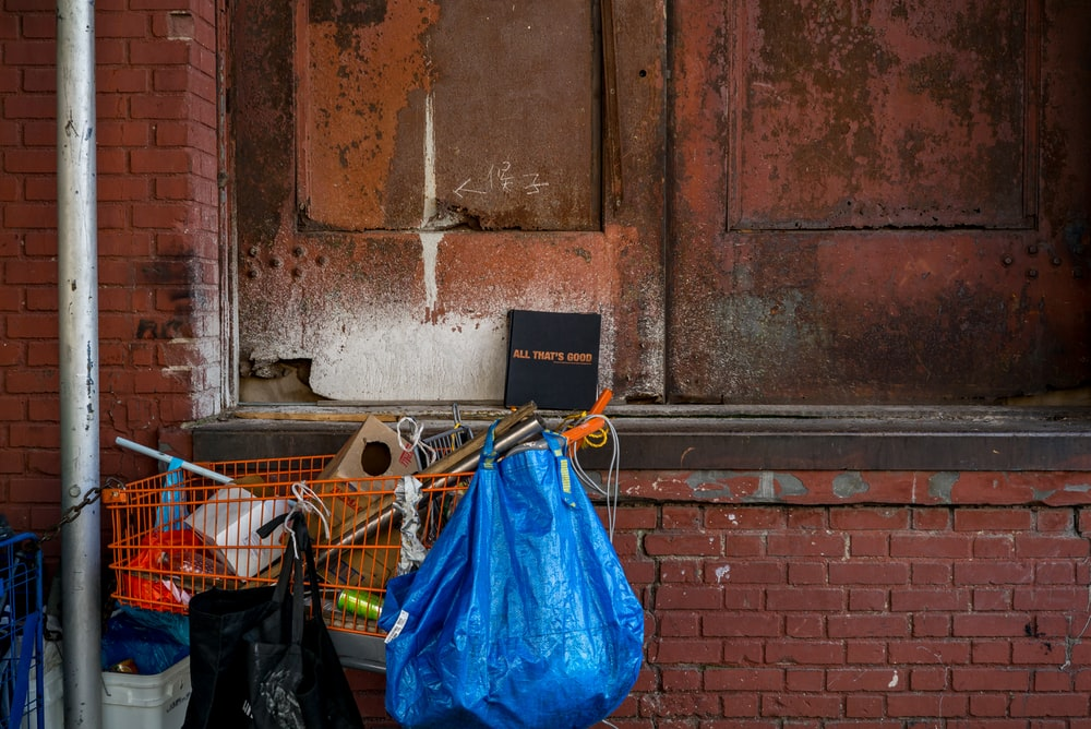 blue bag hanging on orange grocery cart near bricked wall