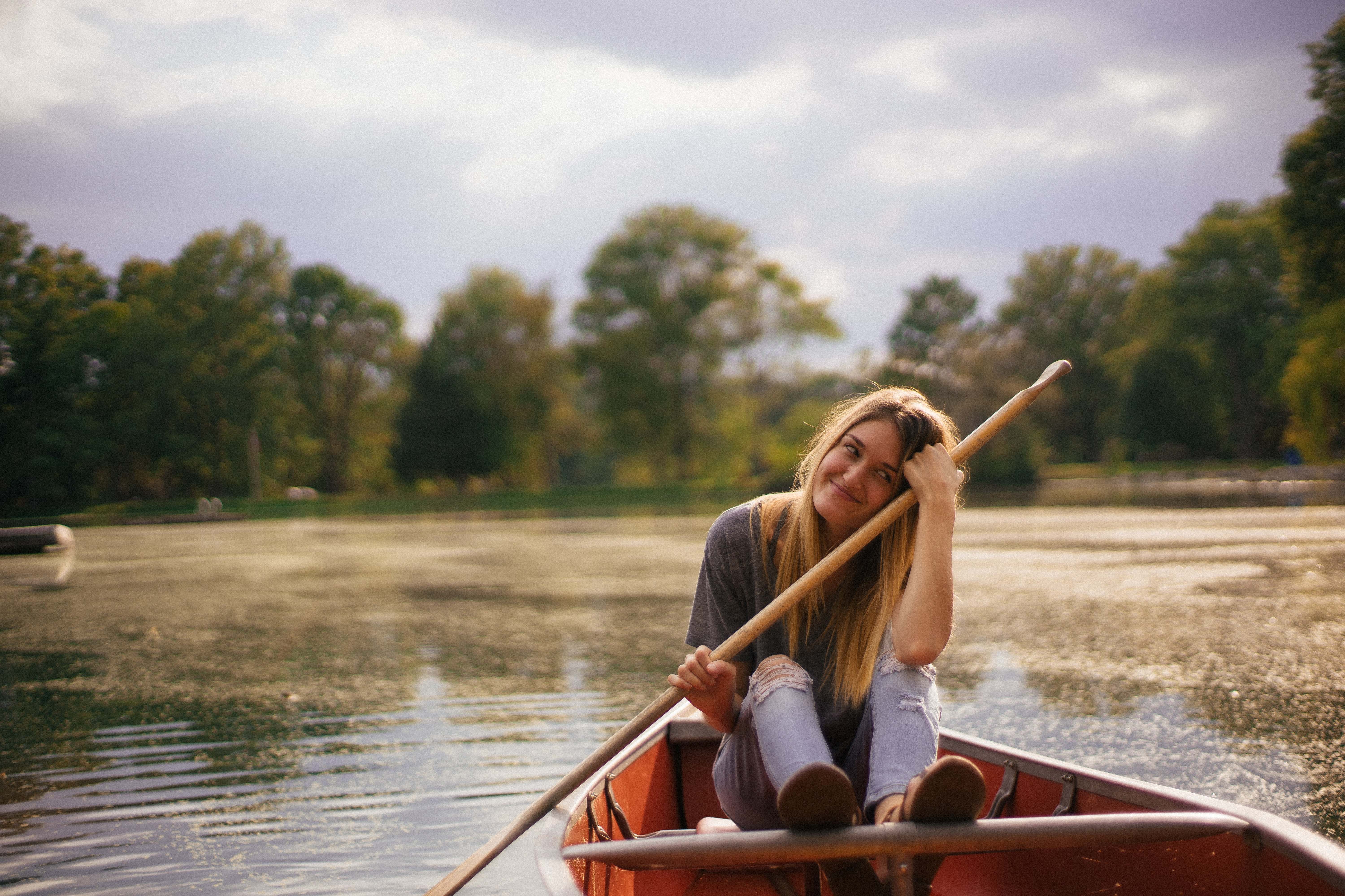 woman riding on boat holding paddle