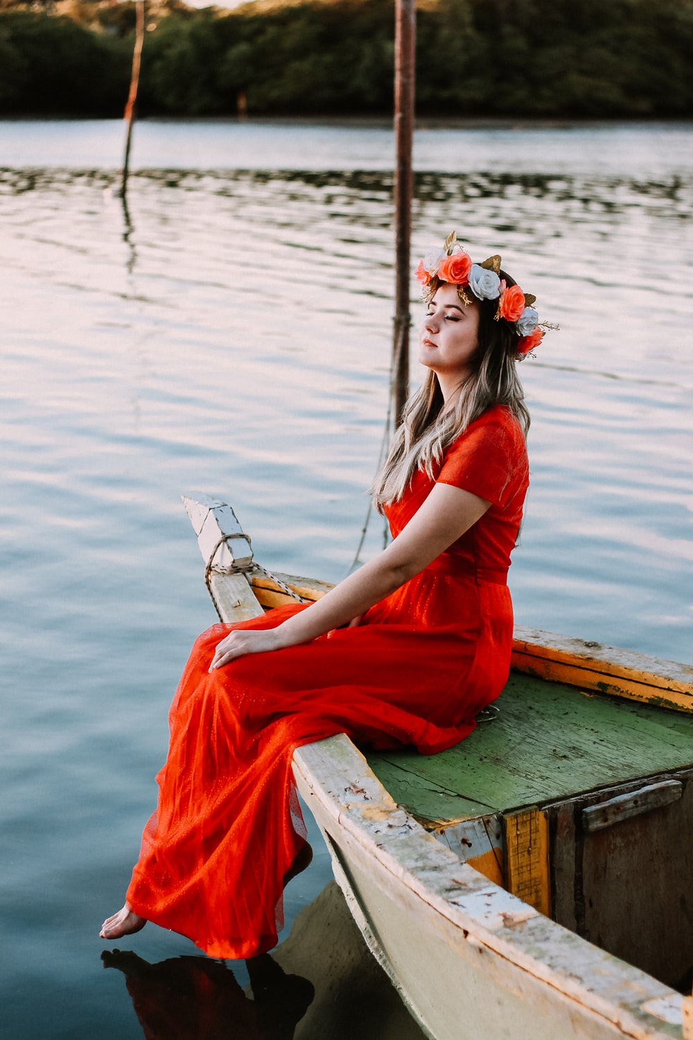 woman sitting on boat in body of water while closing her eyes