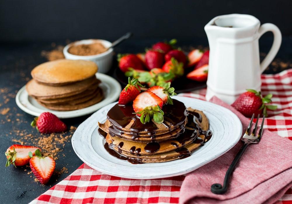 pancake with chocolate syrup on ceramic plate
