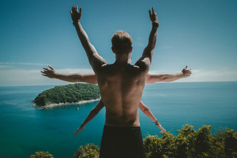 A man standing on a cliff with his arms up, with two other people in front of him.