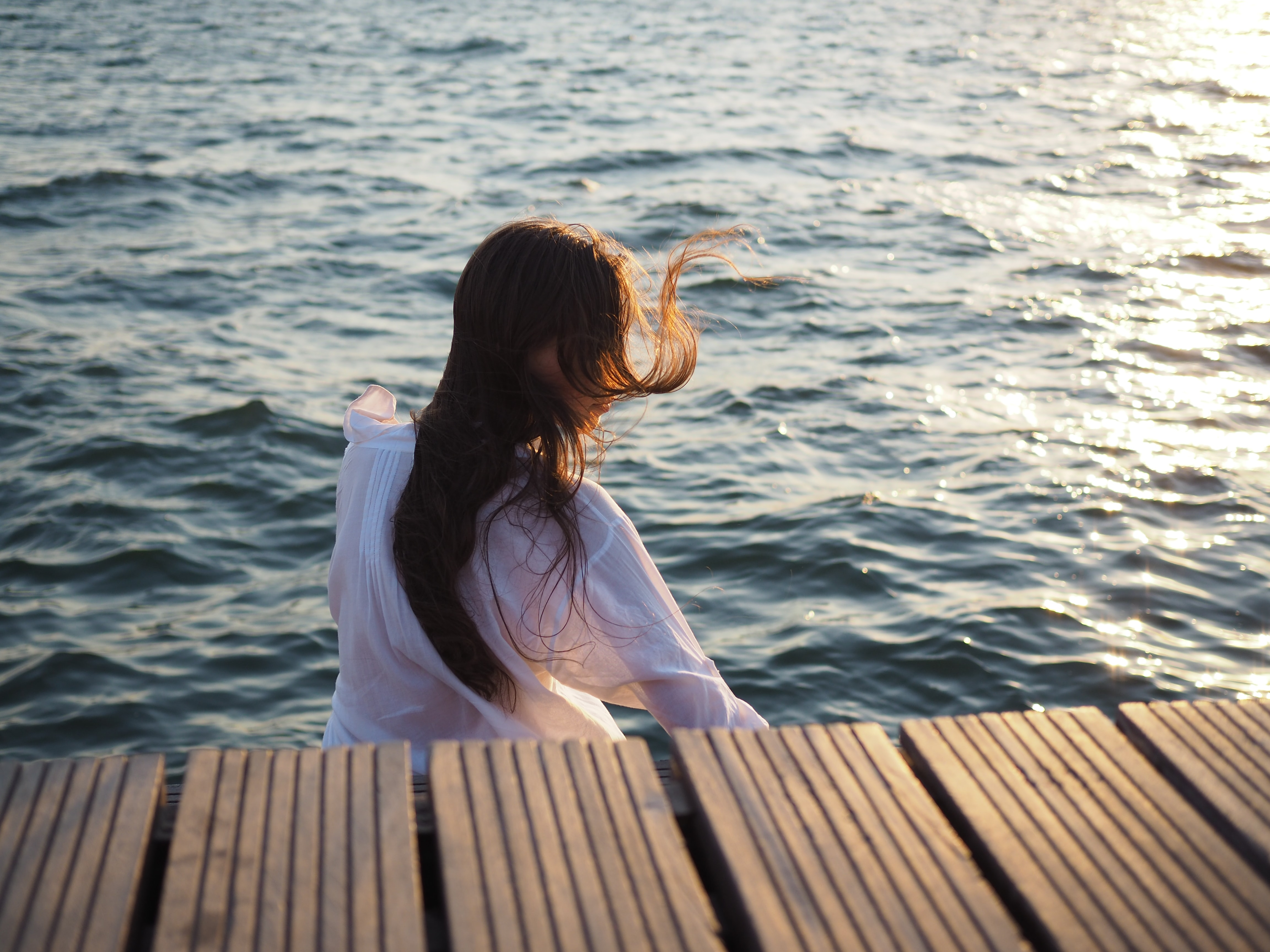 woman wearing white long-sleeved top near body of water