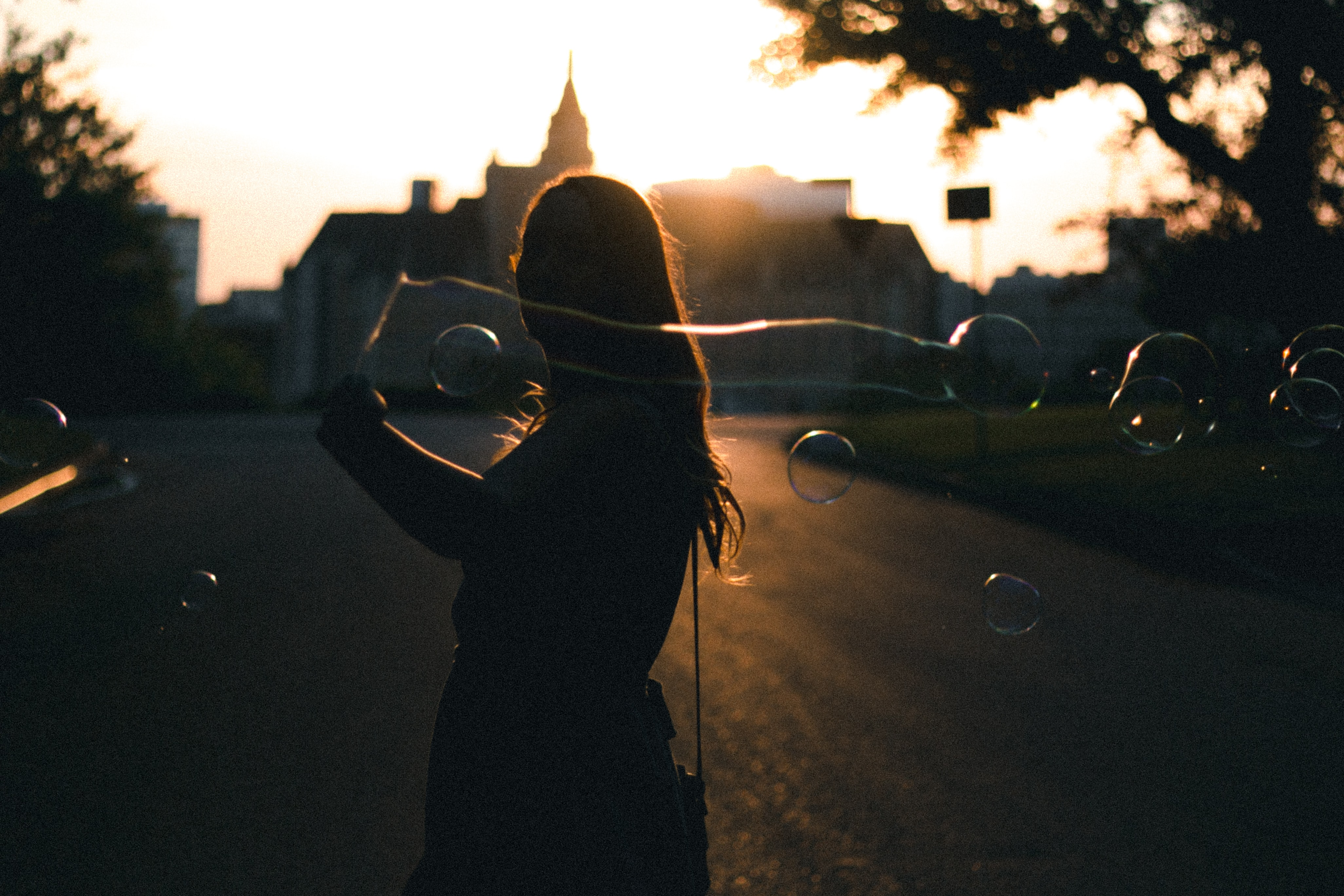 silhouette photo of woman holding bubbles near building during golden hour