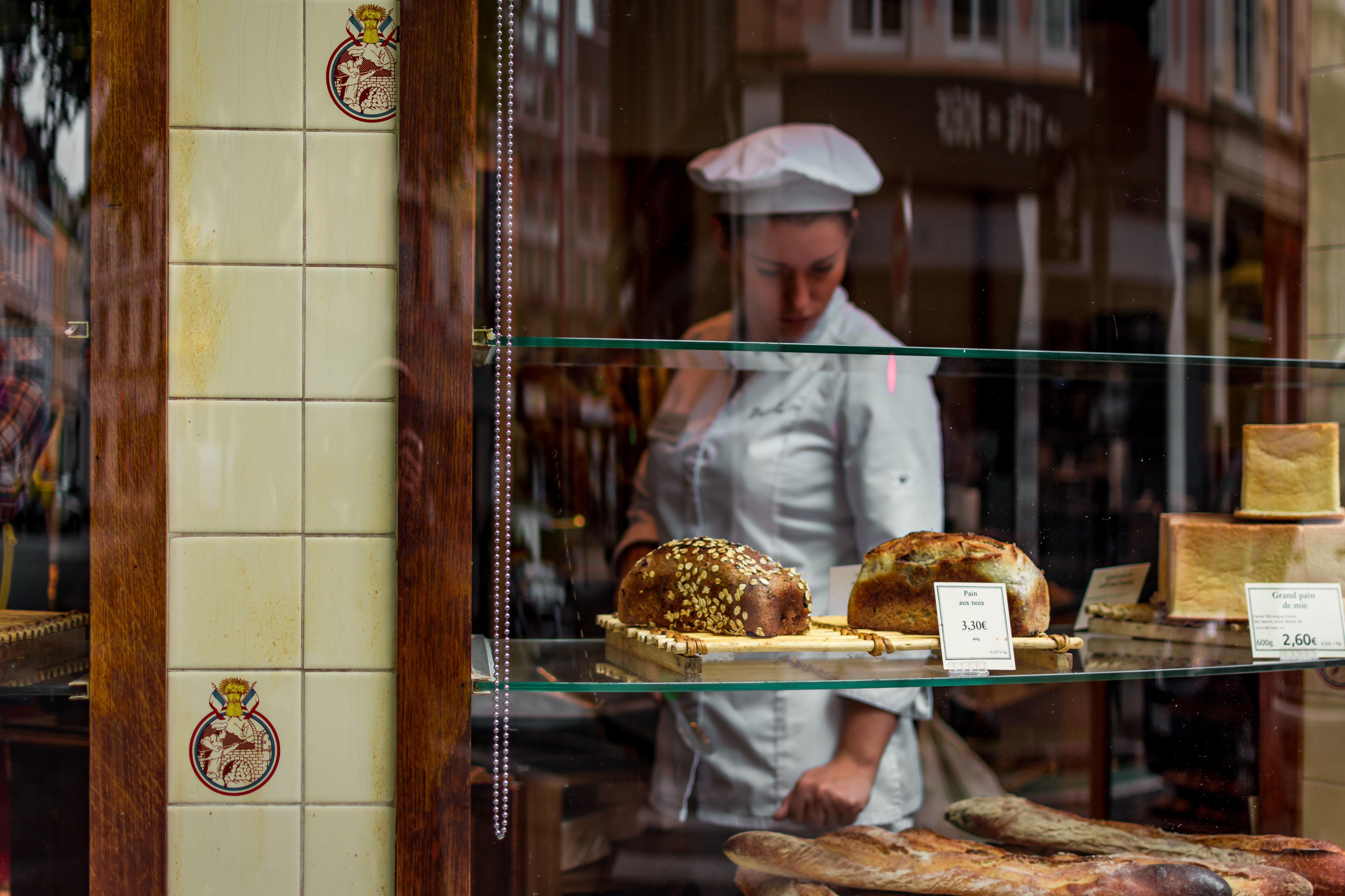 A female baker in a bakery looking at fresh loaves of bread and baguettes in the window in France