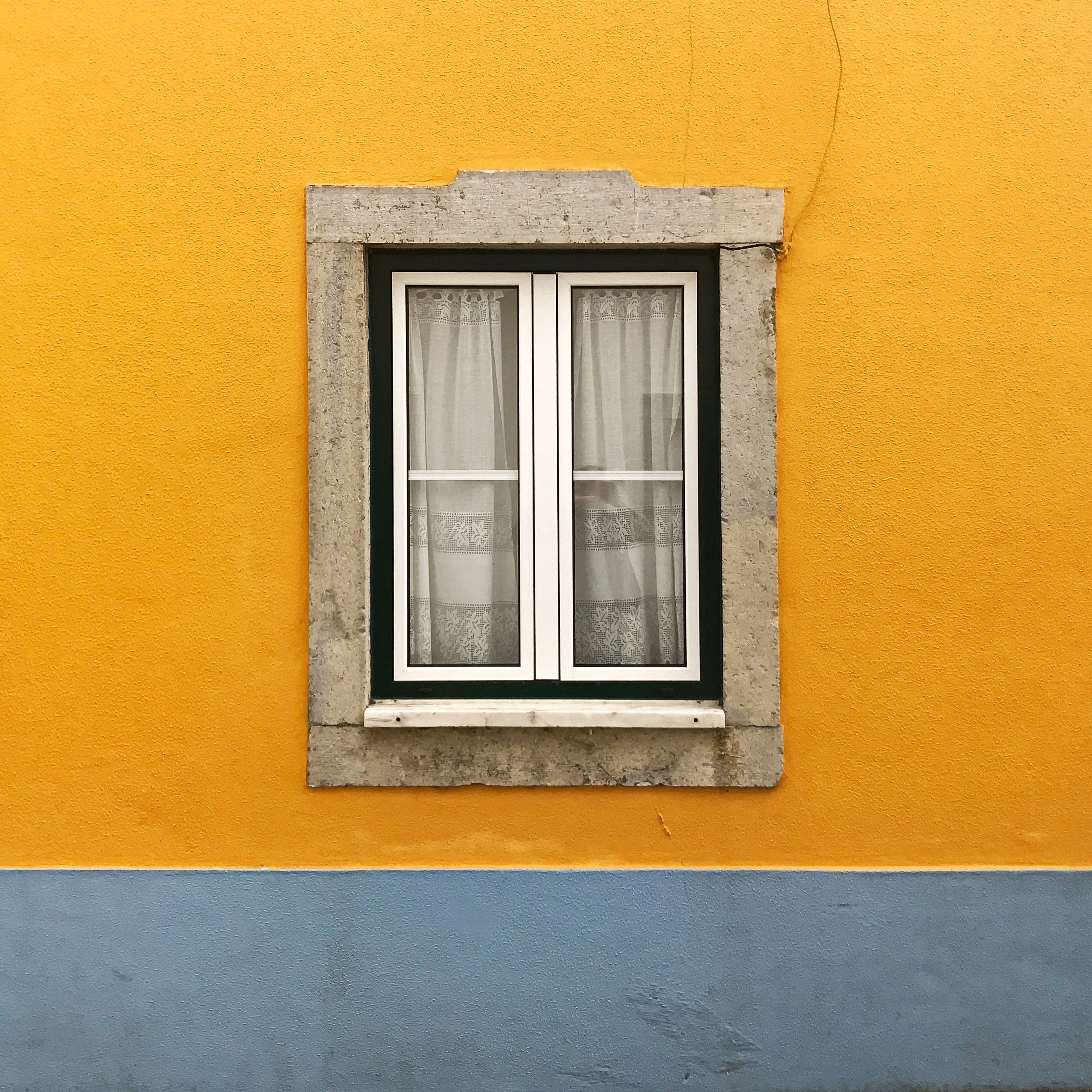 A window in the middle of a yellow building wall.