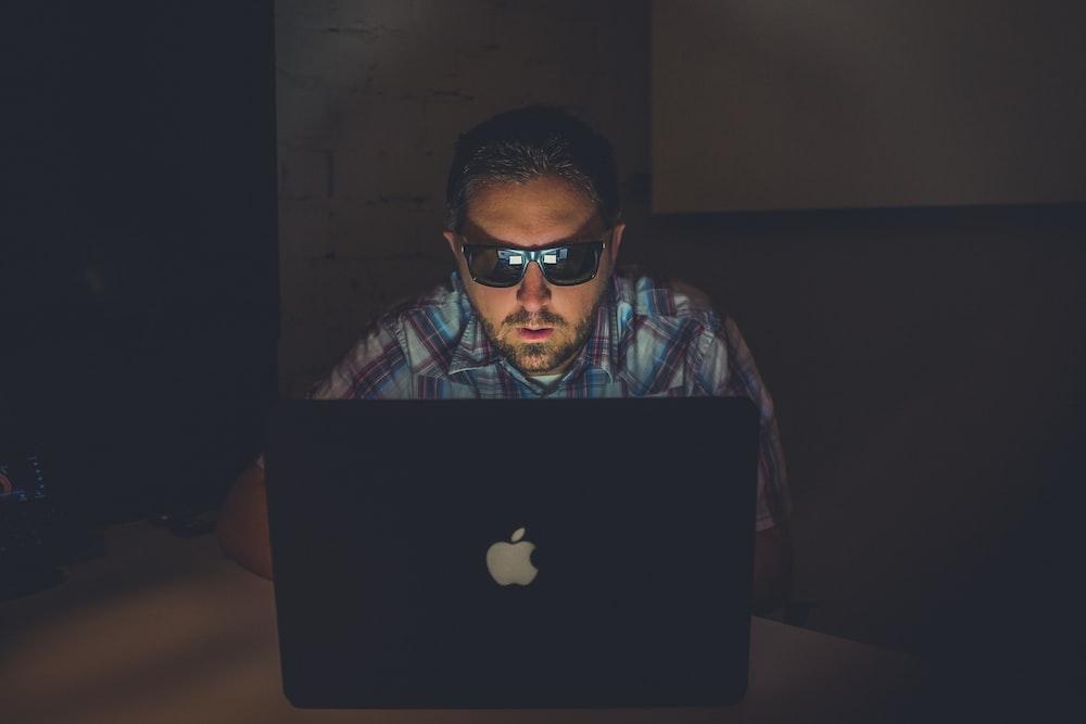 man wearing sunglasses using MacBook