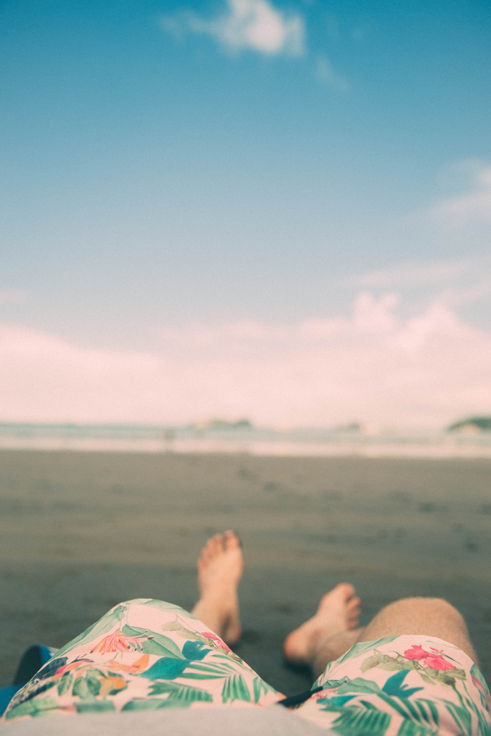 shallow focus photography of person laying on sand