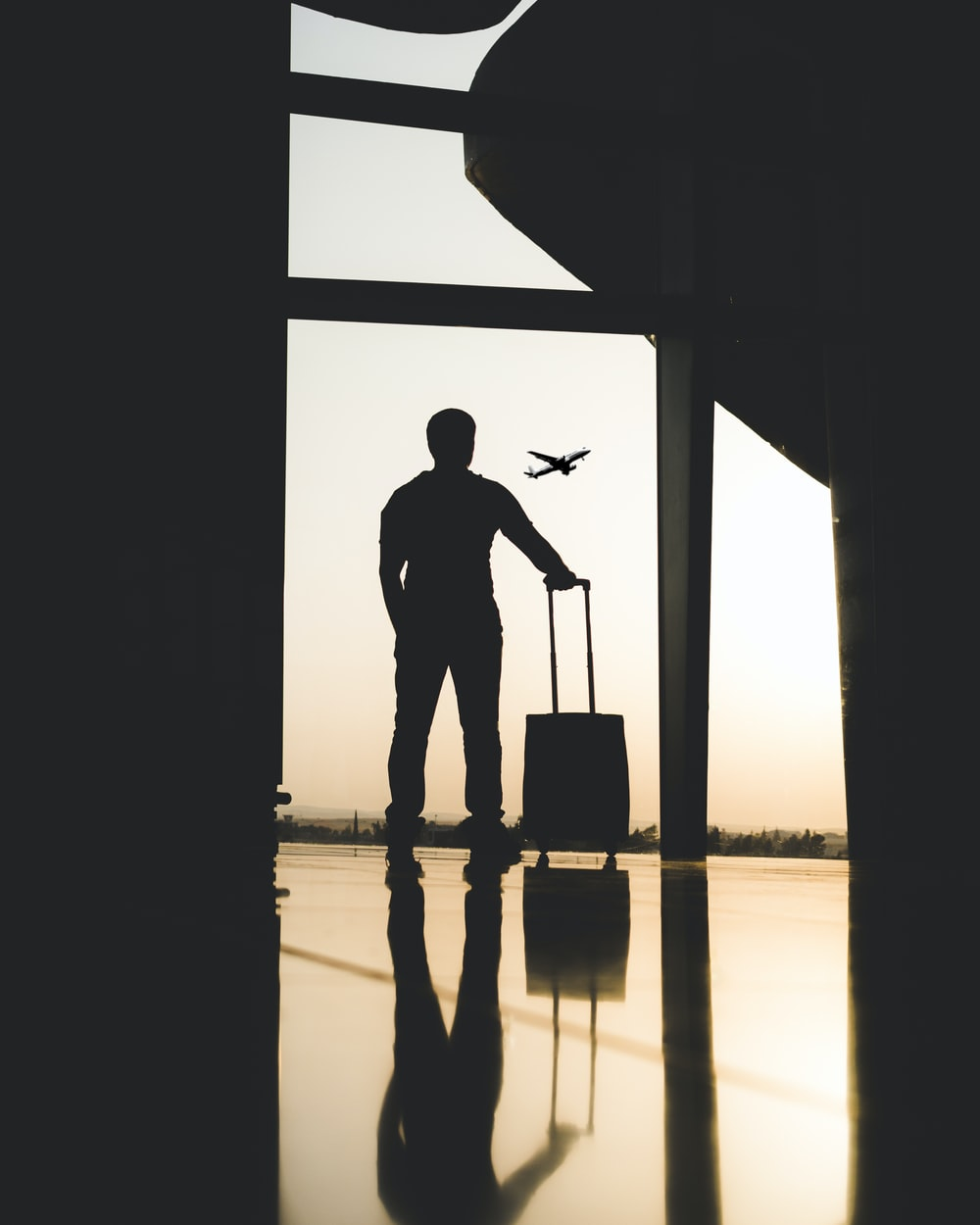 silhouette of man holding luggage inside airport