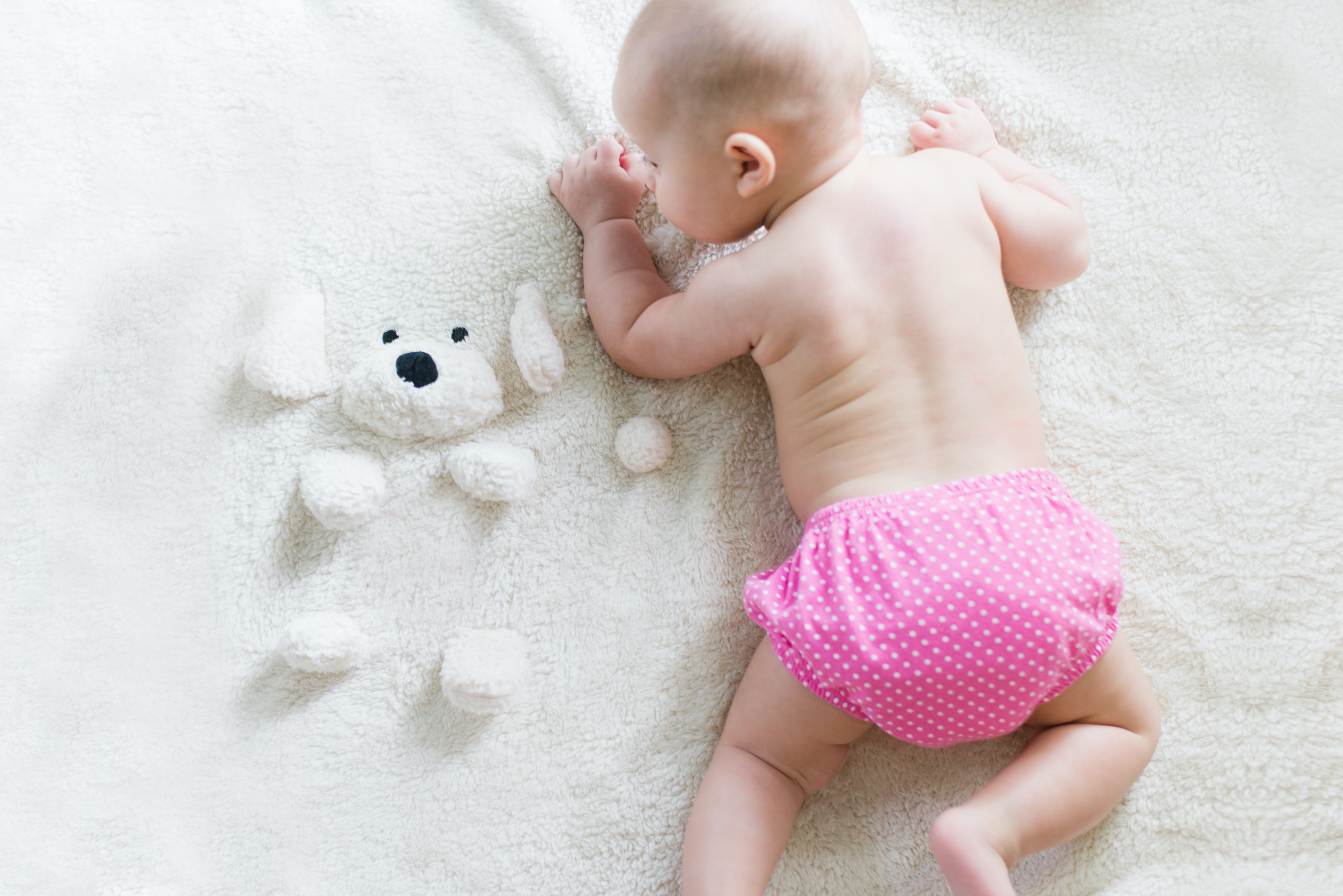 A baby lying on her belly in pink polka dot bottoms.