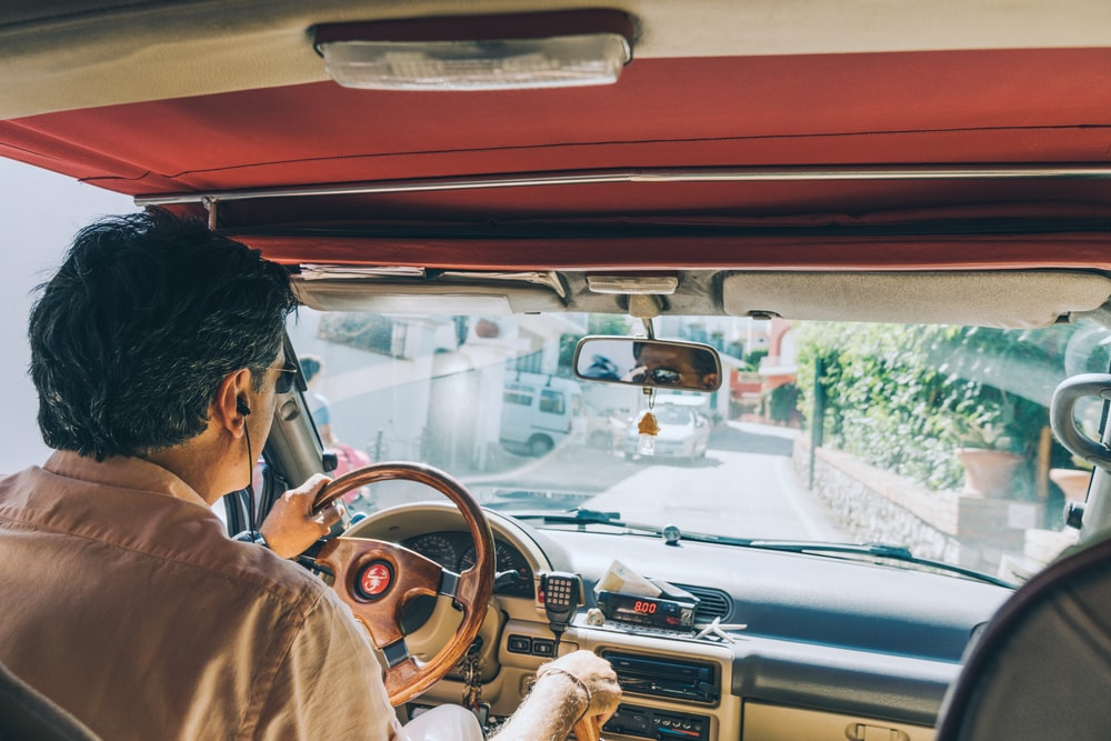 man driving a car during daytime