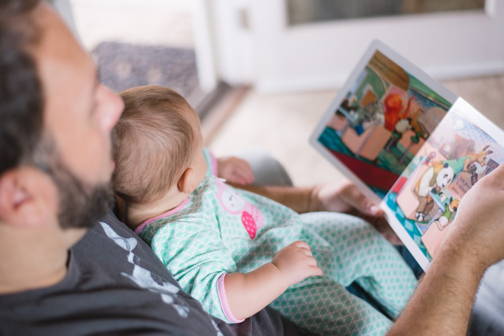 person carrying baby while reading book