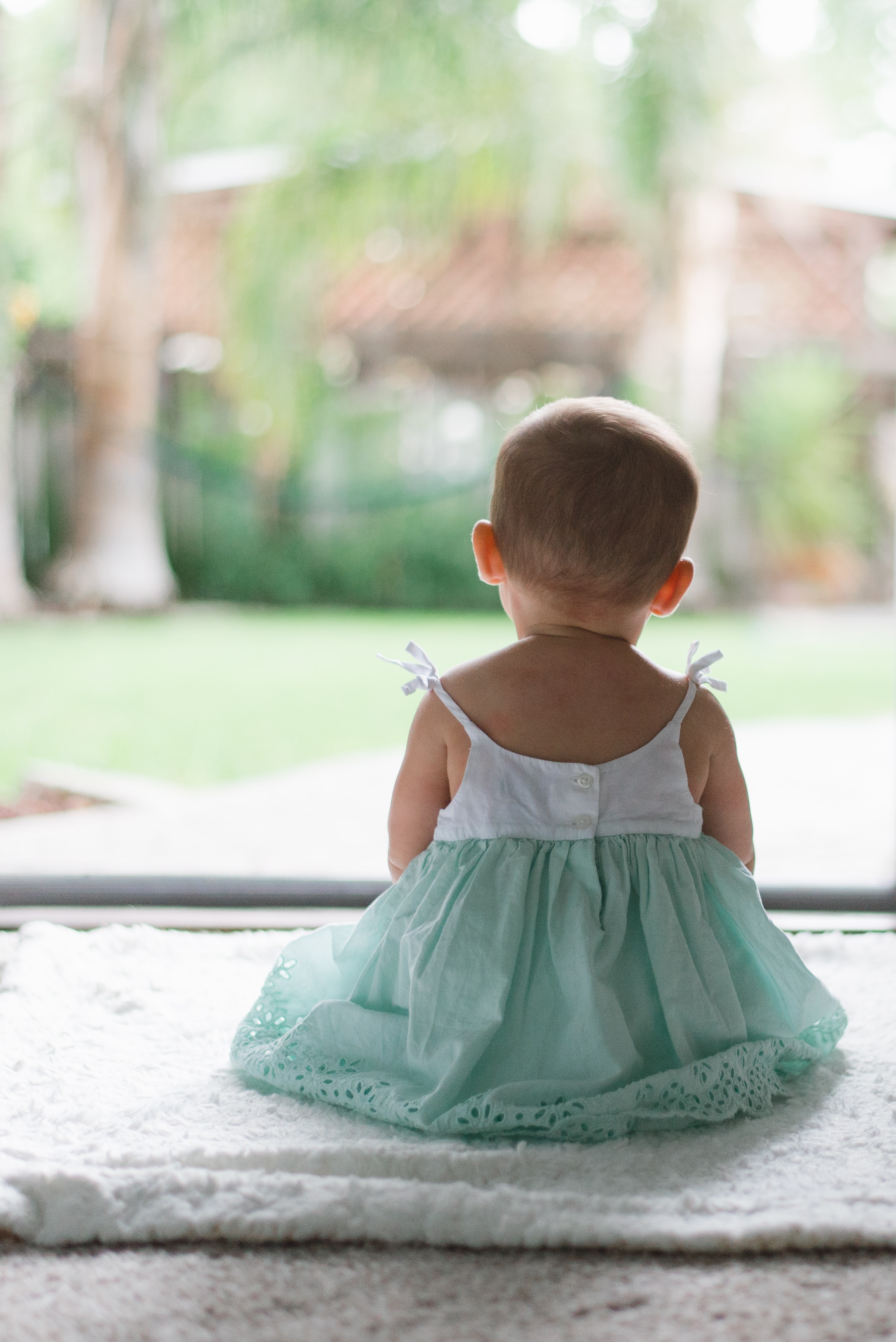 Baby in a dress sits with her back facing camera outside