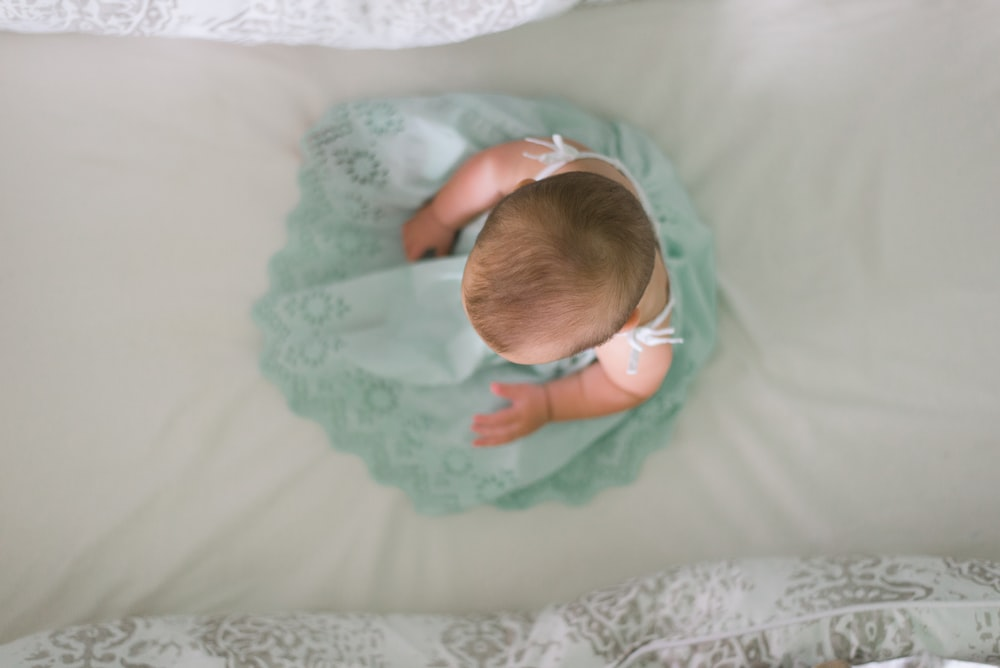 baby sitting on white textile
