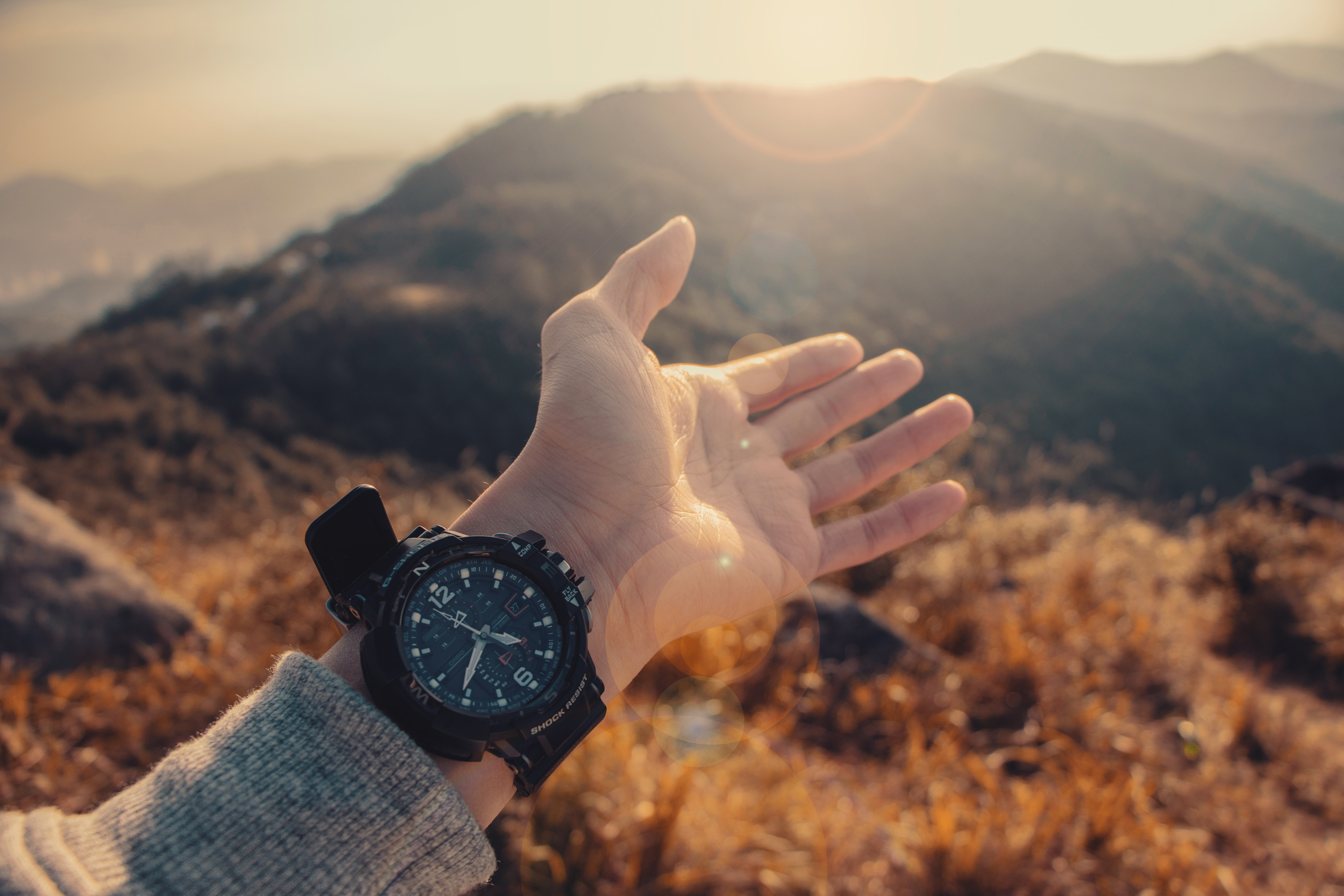 Hand outstretched to a mountain landscape wearing a watch