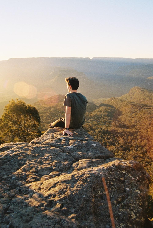 man sitting on rocks looking backwards