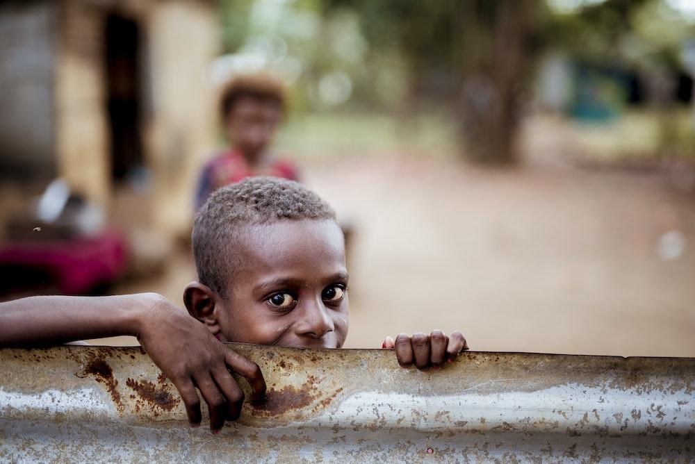 boy holding corrugated sheet