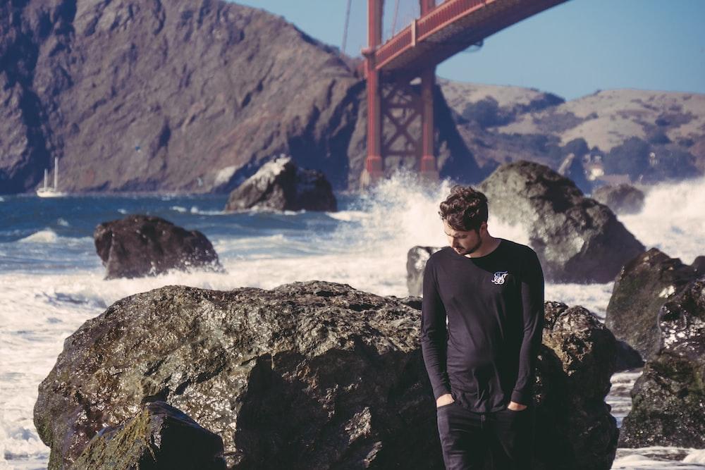 man standing beside black stone with sea waves near red metal bridge during daytime