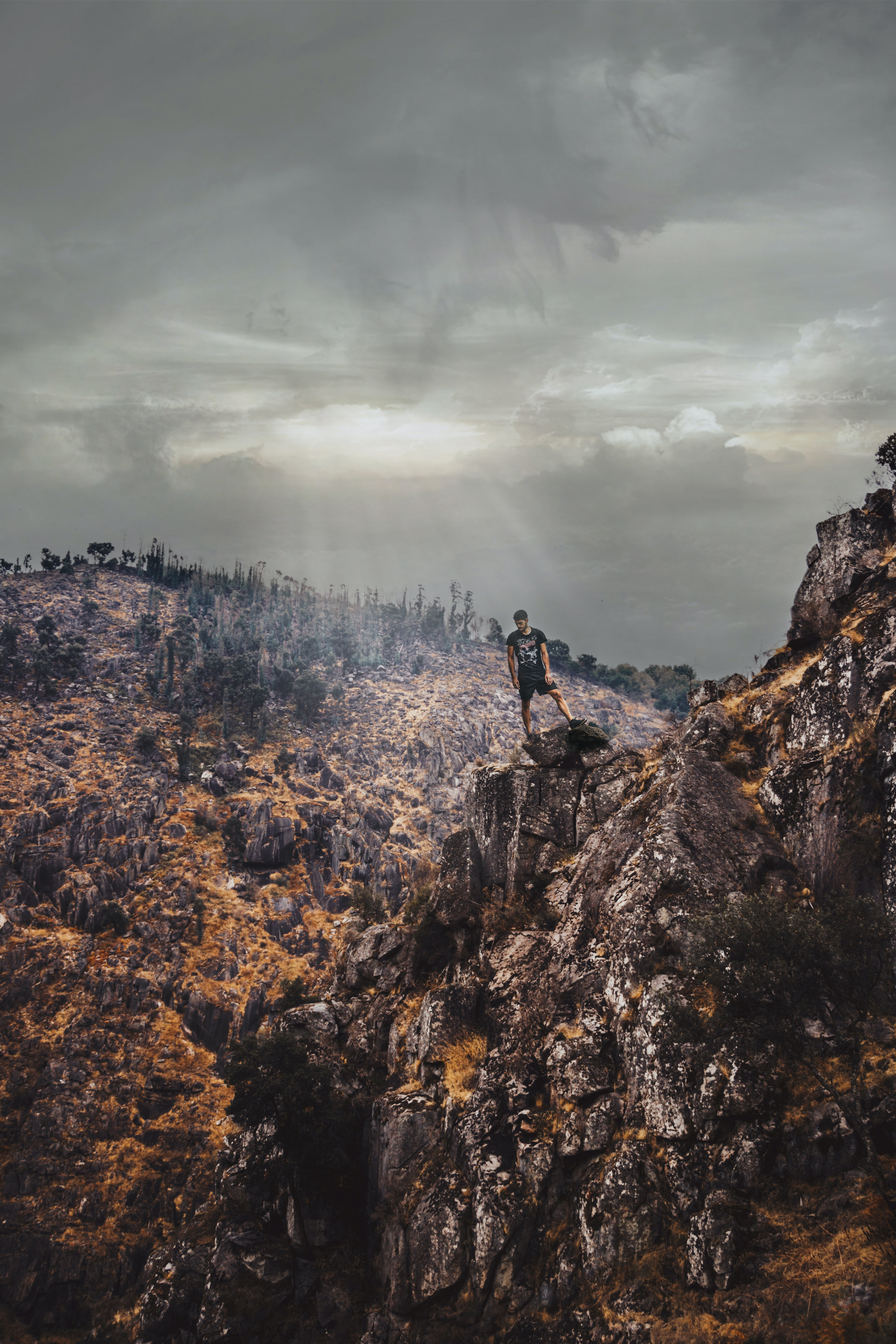 Extreme hiker stands on a rocky mountain ridge on a cloudy day