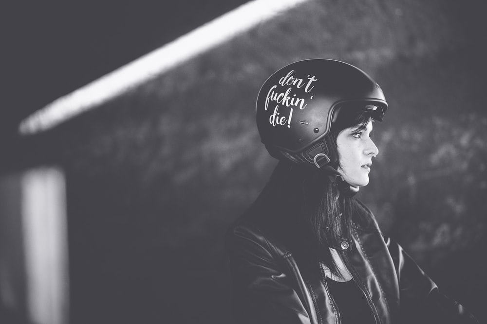 grayscale photography of a woman in leather jacket and half-face motorcycle helmet