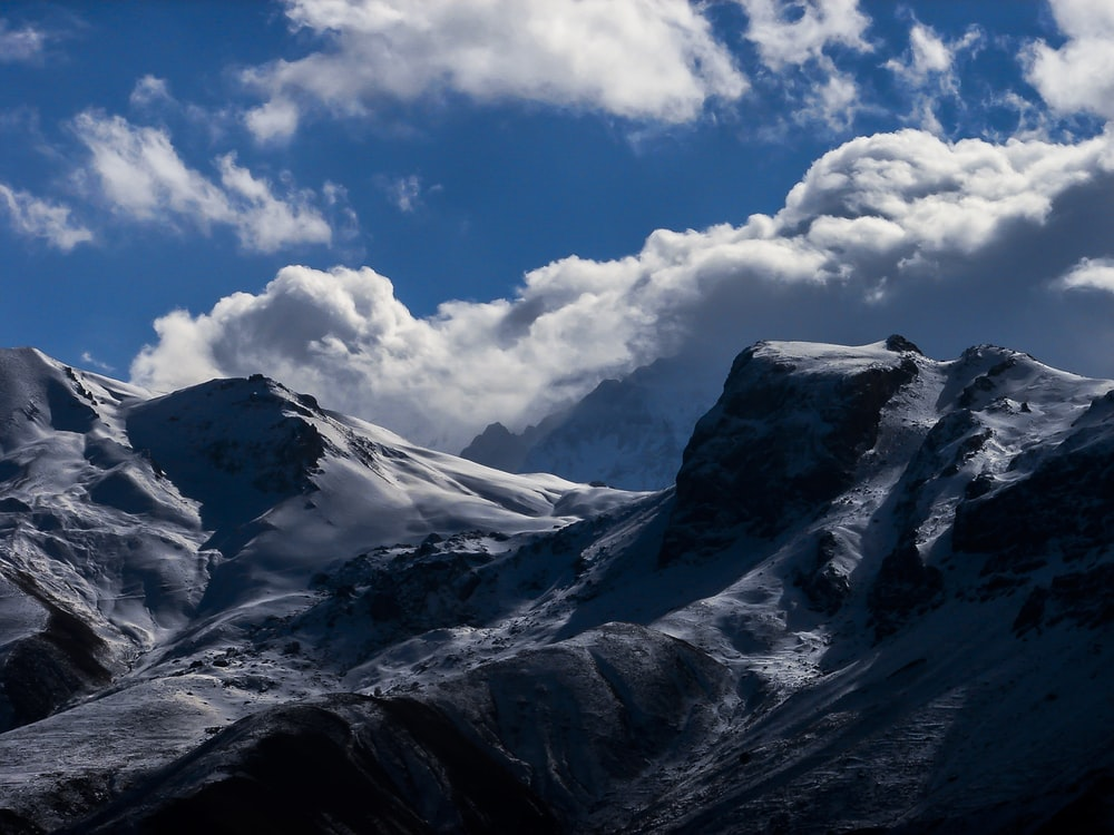 mountain covered with snow under cloudy sky