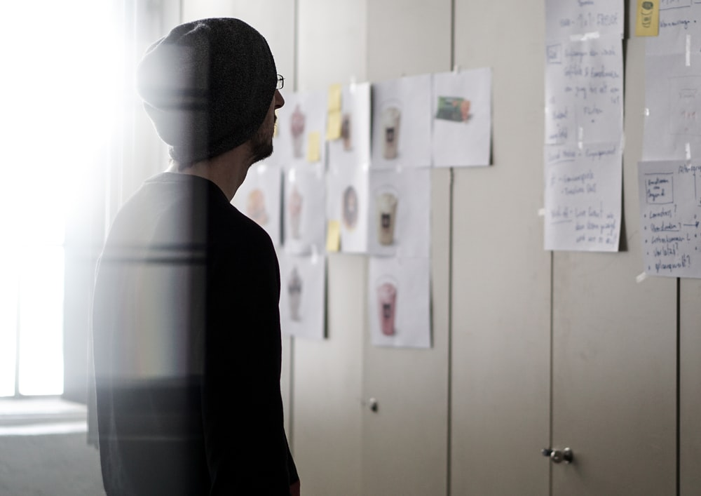 A man staring at office notes on lockers.