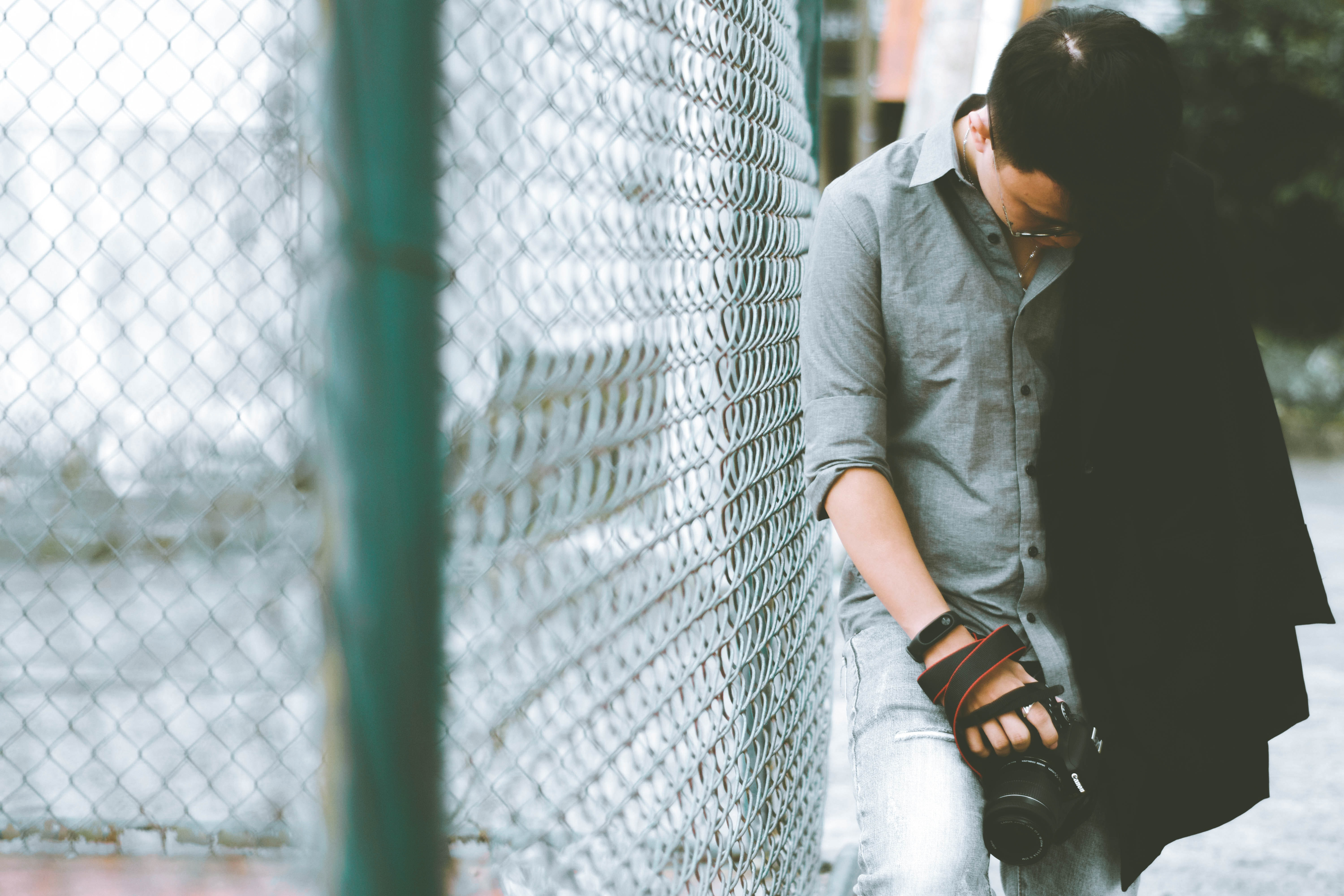 man leaning on cyclone fence while holding DSLR camera