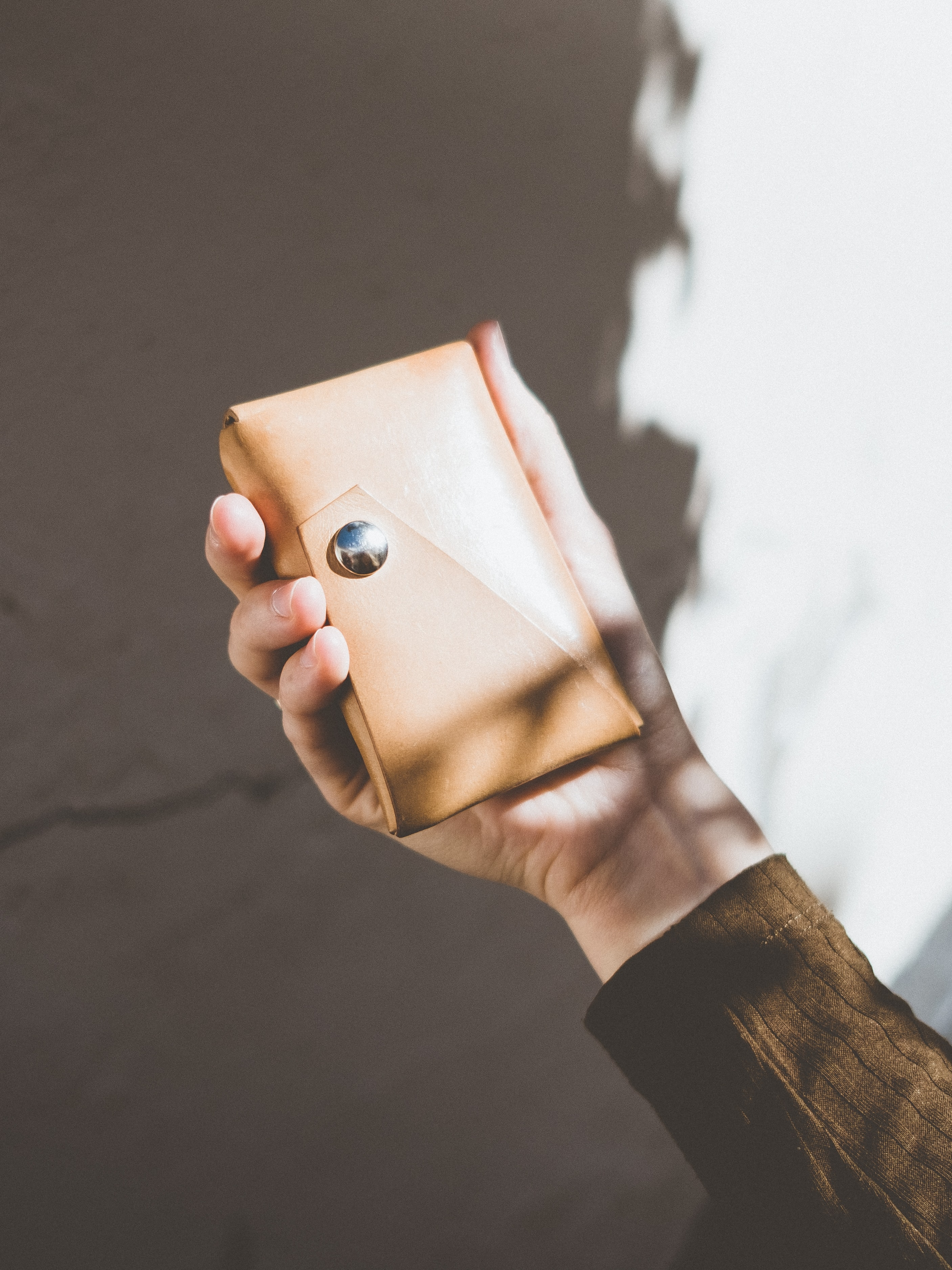 person in brown long-sleeved shirt holding brown leather case
