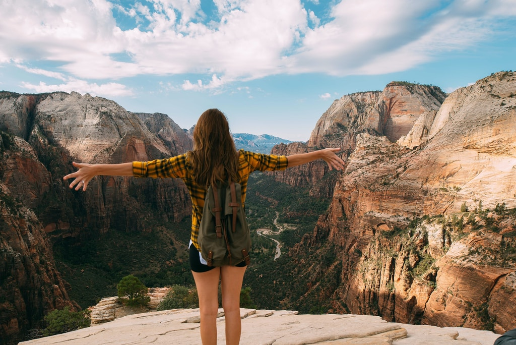 woman spreading her hands white standing on mountain cliff