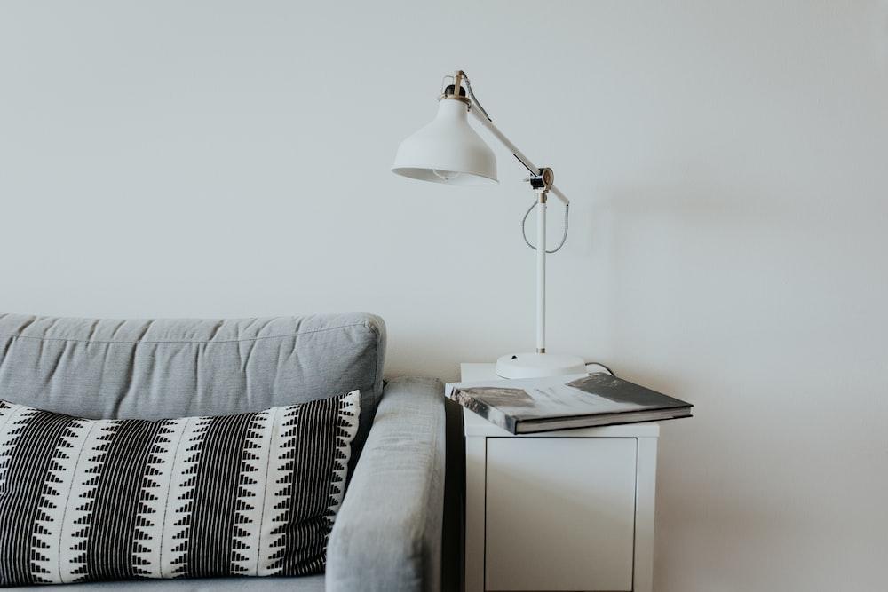 white desk lamp near gray fabric couch