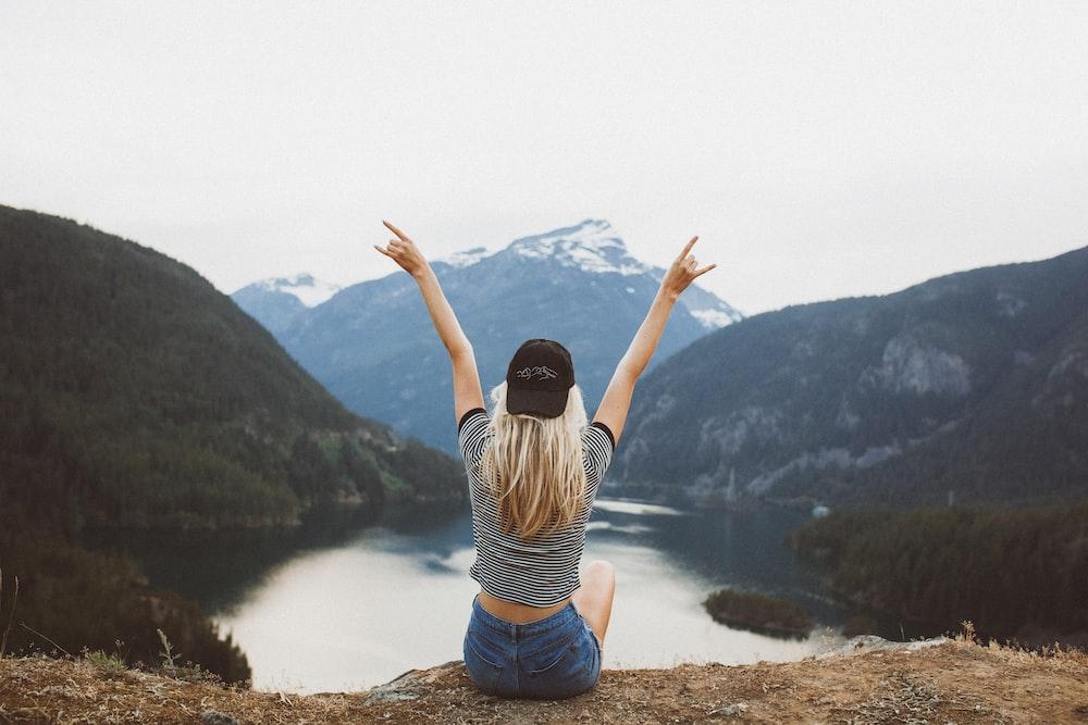 woman sitting on cliff raising both hands
