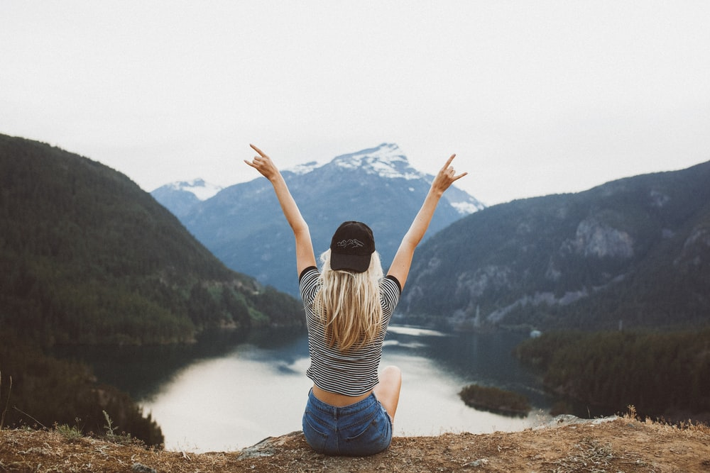 woman sitting on cliff raising both hands